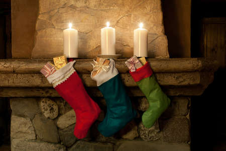 stone fireplace: Christmas stocking on fireplace background. Chimney, candles. Christmas socks, decoration, gifts.
