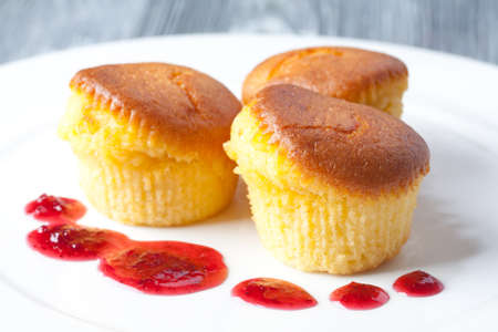 Delicious muffins on a white plate. With a red berry sauce. Gray background. (soft focus) Stock Photo - 35775711