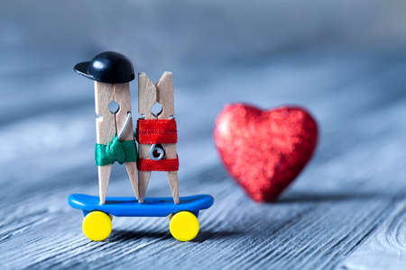 Sport concept. Clothespins: romantic couple. Skateboarding. Red heart background. (Soft focus, vintage paper background, retro style) photo