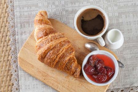 Café, lait et un croissant. Petit-déjeuner. Confiture de fraises.