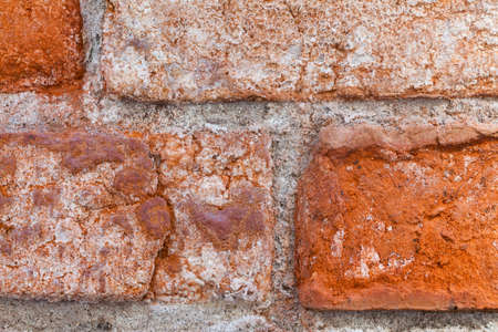 Textured old red wall of brick with traces of rubbing. Stock Photo