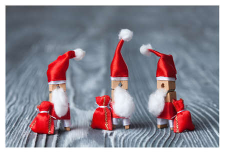 papa noel: Christmas concept - clothespin. Three of Santa Claus. Retro Santa Claus with a few bags of gifts. Father frost. Papa Noel. (soft focus, vintage wood background).