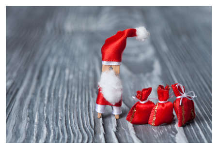 papa noel: Christmas concept - clothespin. Retro Santa Claus with a bag of gifts. Father frost. Papa Noel. (soft focus, vintage wood background). Stock Photo