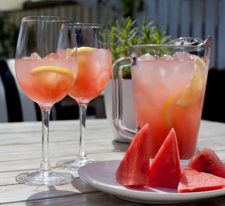 Fruit Lemonade: two glasses, pitcher, watermelon slices on the wooden table. Stock Photo