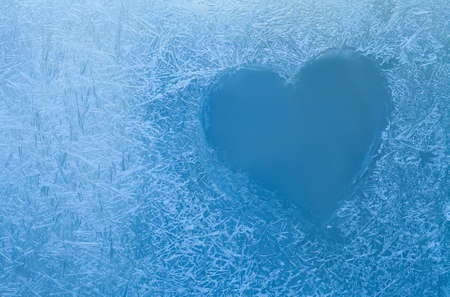 Frozen heart. Frozen glass. Ice flowers. Valentines day. Window frost. Winter window. Frozen window. Craquelure. (Macro. Soft focus. Toned photo).