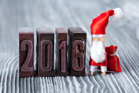 papa noel: 2016 year. written with colored vintage letterpress. Christmas concept - clothespin Santa Claus with a bag of gifts. Father frost. Papa Noel. (soft focus, vintage wood background). Stock Photo