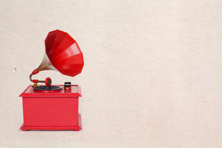 red: Vintage red color gramophone. Retro plastic toy. Old paper background and texture Stock Photo