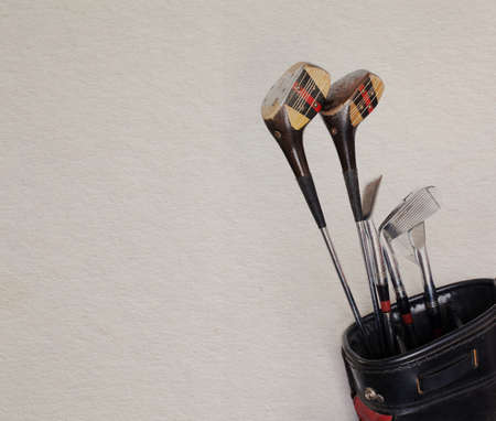 Golf equipment. Retro golf clubs in an old leather bag. Vintage paper background. photo