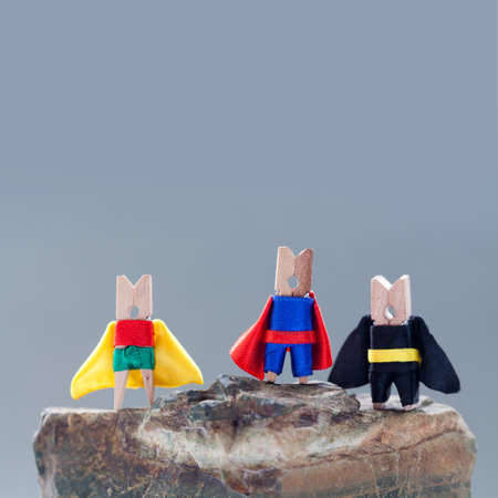 Superheroes on the rock. clothespins. superheroes in blue, black, red, green, yellow and red suit. soft focus, gray background photo