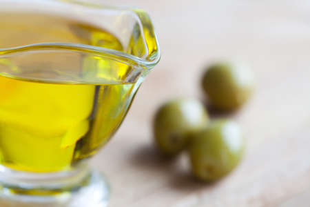 extra virgin olive oil: Olives and olive oil jug. cutting board background. Soft focus