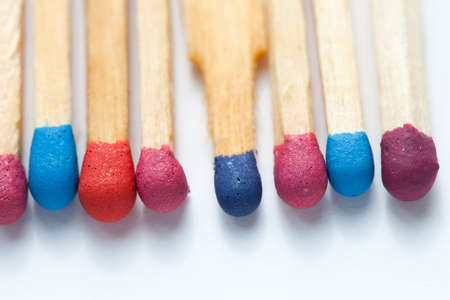 Wooden multicolored matches. White background. Macro view, soft focus photo