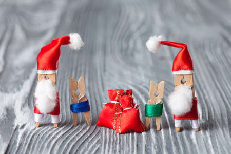 clauses: Christmas concept - clothespin. Santa Clauses with kids and gifts. soft focus, vintage wood background