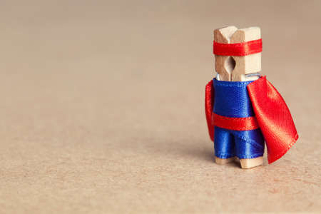 protective suit: Success concept. Clothespin superhero in blue suit and red cape. retro style, soft focus
