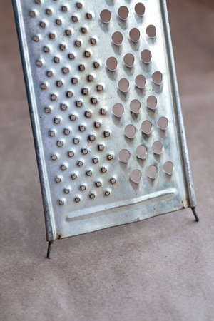 craft background: Retro stainless steel grater on paper craft background. Macro, soft focus