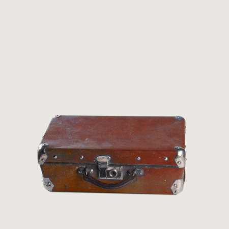 poky: Old-fashioned brown travellers bag, suitcase  with metal corners lying on the floor