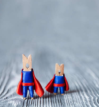 leadership: Clothespins super heroes in blue suit and red cape. Big and small superman.