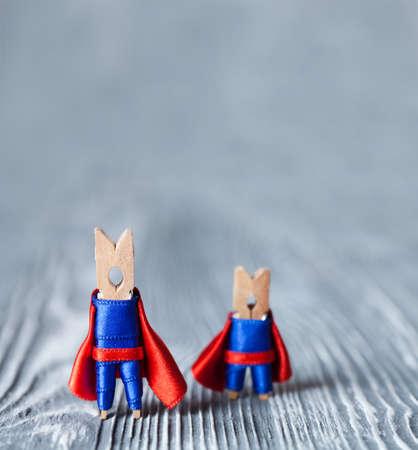 liderazgo: Ganchos de ropa súper héroes en traje azul y capa roja. Superman Grande y pequeño. Foto de archivo