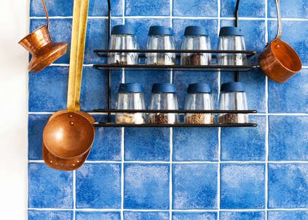 Metal shelf with different seasonings, spices in glass bottles. Kitchenware tools: cooper pot, coffee maker, vintage kitchen soup ladle and skimmer. hanging on blue tile background