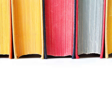 hard cover: Aged colorful book spines. Close up, texture, hard cover. White background. Copy space.