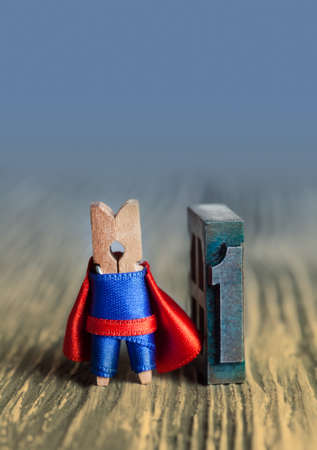 powerful creativity: Leader concept. Clothespin superhero and 1 one written with colored vintage letterpress. Toned background. soft focus, copy space