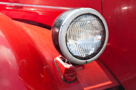 truck repair: Retro style automotive lamp. Red car body background. Macro view, soft focus, Stock Photo