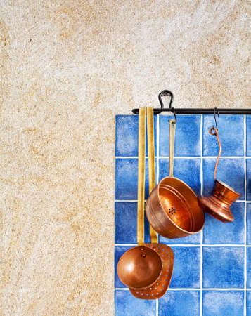 fireproof: Coffee maker, spoon, skimmer, colander. Blue tiles ceramic background, aged sand wall texture. copy space.