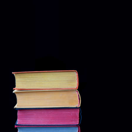 hard cover: Colorful books. Yellow, violet, blue, yellow pages. Close up, textures and detailes, hard cover. Black background. Copy space. Isolated