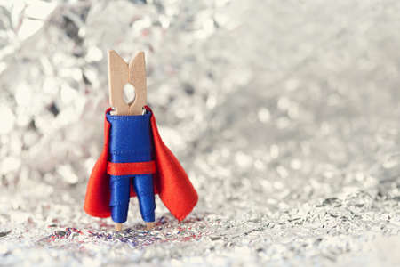superheroine: Clothespin superhero in blue suit and red cape. shallow dof. soft background. Stock Photo