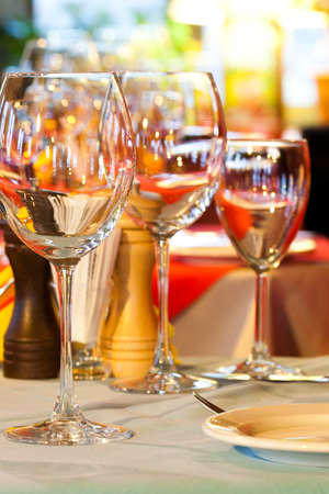 romantic evening with wine: Restaurant service. Served table charger. Wine glasses, plate and cutlery. Bright blurred and soft interior, tableware. romantic evening dinner. vertical. soft focus.