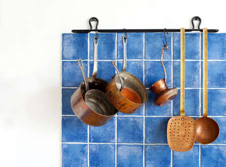 fireproof: Kitchen appliances. Hanging retro design copper kitchenware set. Pots, stewpots, saucepans, coffee maker, kitchen spoon, skimmer hanging on. Blue tiles wall background.