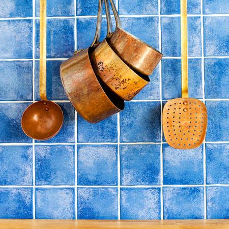 skimmer: copper utensils. cookware, kitchenware set. Pots, kitchen spoon, skimmer hanging on. Blue tile wall, wood background.
