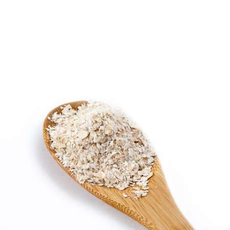 Retro style wooden spoon with oat bran. Macro view. Isolated on white background.