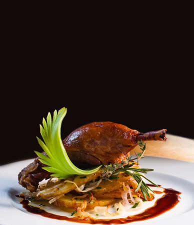 roast duck: Baked delicatessen duck pestle with fried potatoes on white plate. Stock Photo