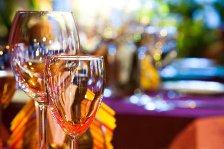 Restaurant interior with wine glasses, closeup. Bright blurred background.