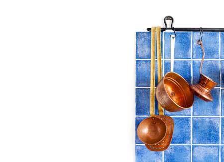 utensilios de cocina: utensilios de bronce retro. utensilios de cocina, jefe de cocina conjunto en la pared azulejos azul.