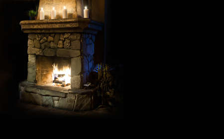 burning fireplace: Chimney place with candles and real fire and flame