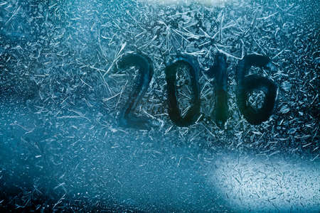 New year greetings card concept. ice flowers, frost pattern and texture on bluew glass window. close-up. soft focus