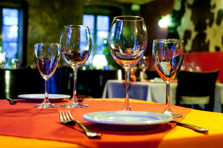 colorful still life: Served table. Romantic restaurant interior with a bright tablecloth, napkins, wine glasses and cutlery. colorful still life and service concept photography Stock Photo