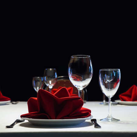 Served table. Romantic restaurant interior with a bright tablecloth, napkins, wine glasses and cutlery. colorful still life and service concept photography Standard-Bild