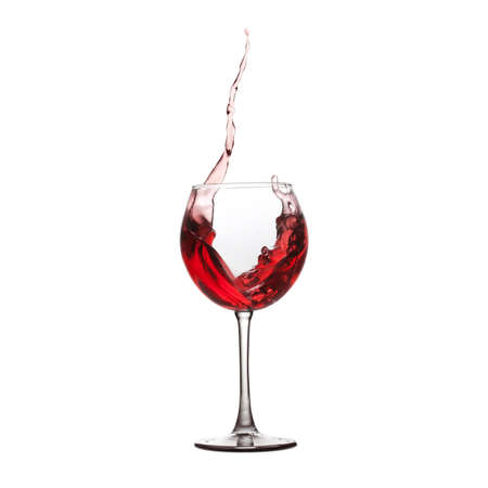 splashing red wine in wineglass. white background copy space
