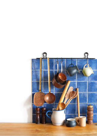 Kitchen brass utensils, chef accessories. Hanging copper kitchenware set. Blue tiles ceramic wall. spoon, pitchers, spices on the wooden table. copy space. Stock Photo