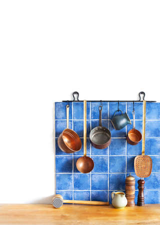 Kitchen brass utensils, chef accessories. Hanging copper kitchenware set. Blue tiles ceramic wall. spoon, pitchers, spices on the wooden table. White background. copy space.