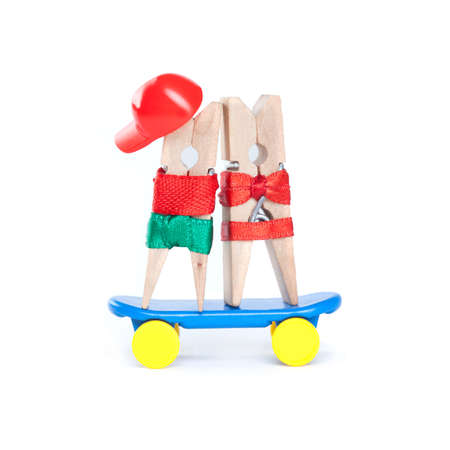 teen girls: Clothespin skateboarders. Skating boy, girl on blue skate board. Man in a red baseball cap, t-shirt, green shorts. Woman in a red bikini. White background. Sport, love, friendship concept.