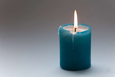 solitariness: Turquoise candle with flames in motion. Macro view. soft focus. gradient gray background. Memorial day concept. copy space