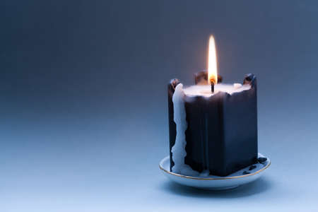 copy space: Black candle on dark blue gradient background. Greeting holiday card template. copy space