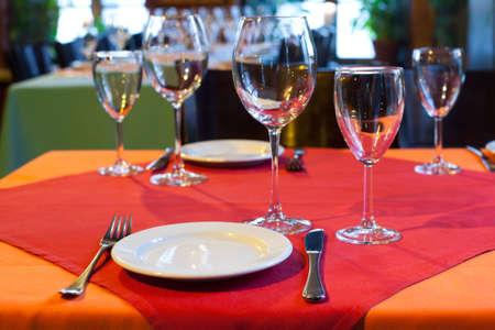 fork glasses: Served table in restaurant. white plate knife fork and wine glasses on red napkin. romantic interior