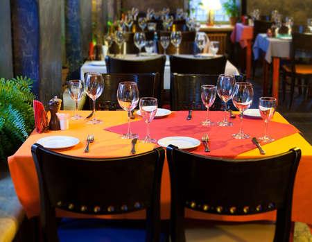 fork glasses: Served table in restaurant. white plate knife fork and wine glasses on red napkin. romantic interior concept
