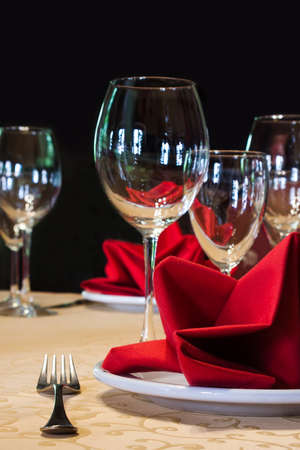 fork glasses: Served white plate with fork and wine glasses. red napkin. black background, soft focus