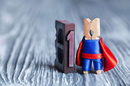 superiority: Leader concept. Clothespin superhero and 1 one written with colored vintage letterpress.  soft focus,