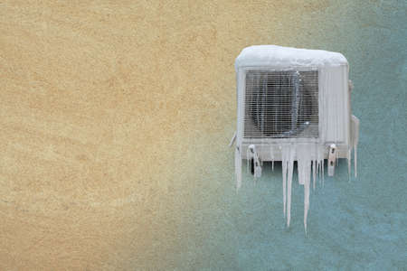 Frozen air conditioner with icicles. Heating and cooling concept. Vintage sand stone wall background. Toned photo. copyspace Stok Fotoğraf